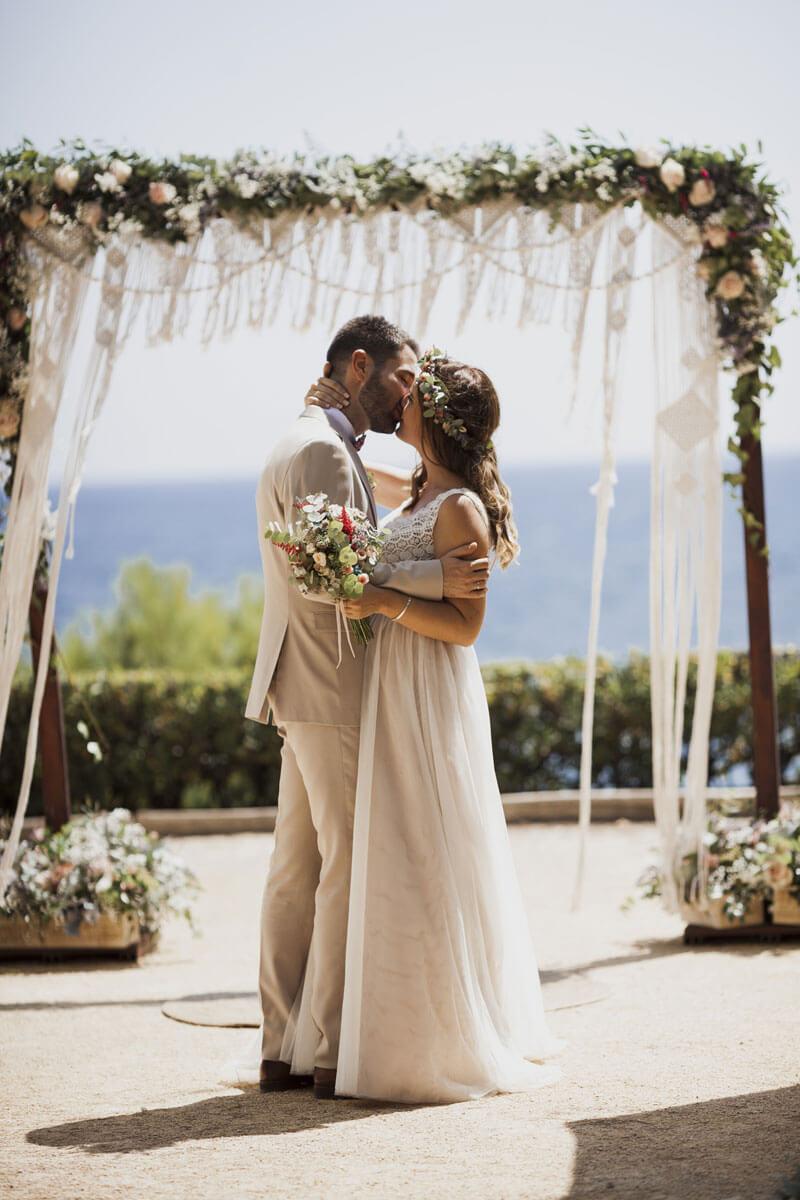 Beso de novios bajo el decorado del altar